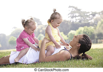 mother playing with daughters in the park in summer