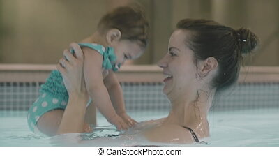 Mother playing with her baby girl in the pool. 4K Footage....