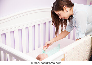 Mother playing with her baby in a crib
