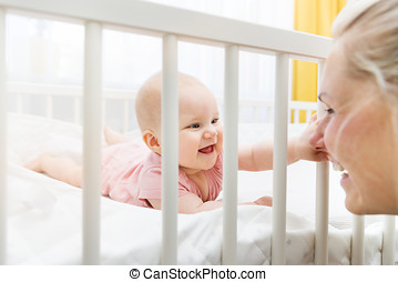 mother playing with her baby in crib and having fun together