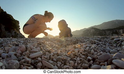 Mother playing with her baby kid on the beach in sunset lights