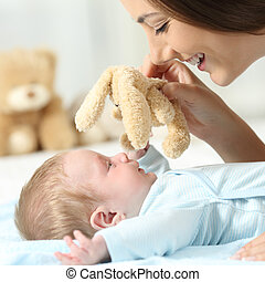 Mother playing with her baby with a teddy
