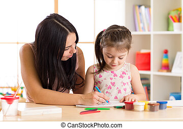Mother playing with her child daughter, drawing together