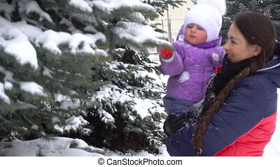 mother playing with her daughter outdoors at winter time and shakes snow from the trees