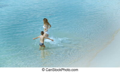 Mother playing with her little son and running in the sea at tropical beach