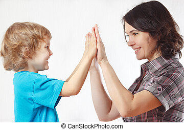 Mother playing with her little son on a white background