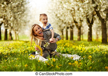 Mother playing with her son in a blossoming orchard