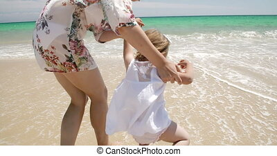 Mother playing with her young daughter at the sea leading...