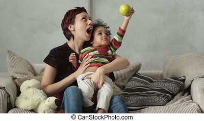 Mother playing with mixed race toddler son on sofa