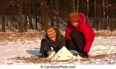 Mother playing with son in winter park