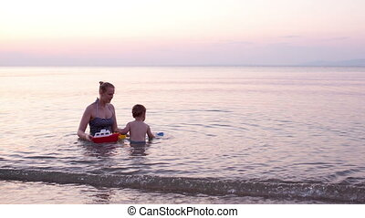 Mother playing with young son with toy boat