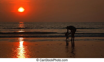 Mother Plays with Baby on the Beach at Sunset. FullHD 1080p video