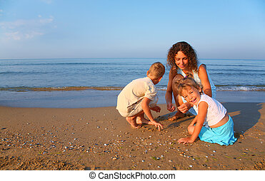Mother plays with children finding shells on sand at edge of sea