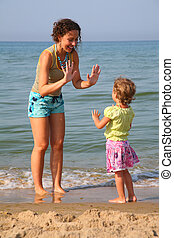 Mother plays with daughter on beach