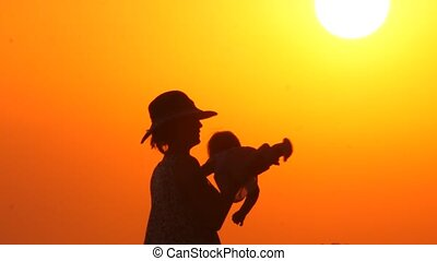 Mother plays with daughter on the beach during sunset. Happy parenting concept. Abstract background. Summer vacation with child. Happy father with cheerful kid on hands with sunset background