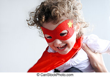 Mother plays with little superhero child girl
