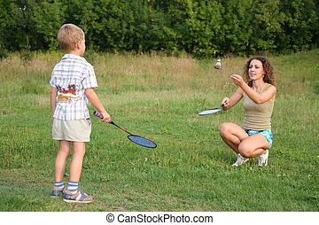 Mother plays with son in badminton