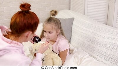 mother pouring antipyretic syrup to sick little child -...