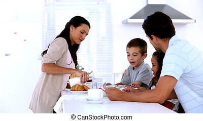 Mother pouring milk at family breakfast in the kitchen