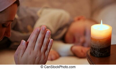 Mother praying at the bedside of the sleeping baby