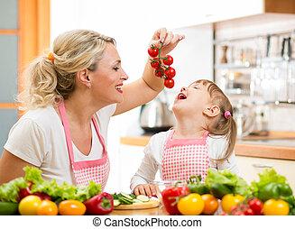 mother preparing dinner and feeding kid tomato in kitchen