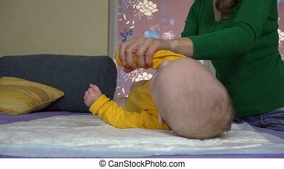 Mother preparing to massage little baby daughter . 4K