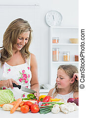 Mother preparing vegetable on the table in the kitchen - ...