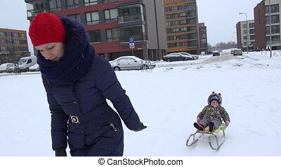 Mother pull sled with baby daughter at winter time in park. 4K