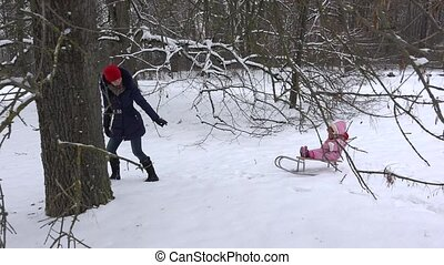 mother pull sled with baby on snow between trees in winter...