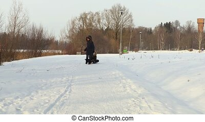 Mother pull sled with daughter on snow cowered path in cold winter day