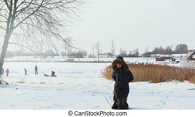 Mother pulling sled with happy child in winter