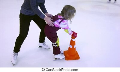 Mother push little girl on skates to ice rink border