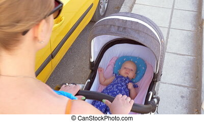 Mother pushing baby carriage in the street - Young mother...
