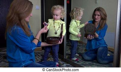 Mother put ring on her toddler daughter girl finger near mirror