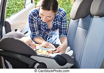 Mother Putting Baby Into Car Seat For Journey