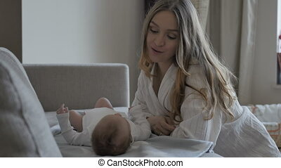 Mother putting baby on sofa