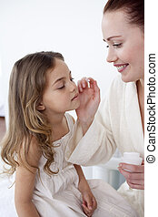 Mother putting cream on her daughter\'s face