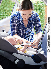 Mother Putting Crying Baby Into Car Seat For Journey