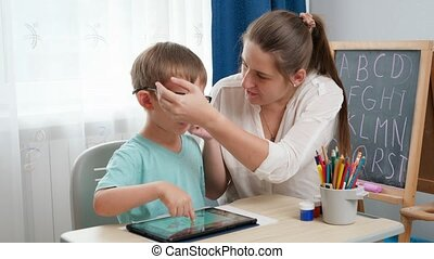 Mother putting eyeglasses on her smart son playing on tablet computer and doing homework. Child problem with eyes and sight