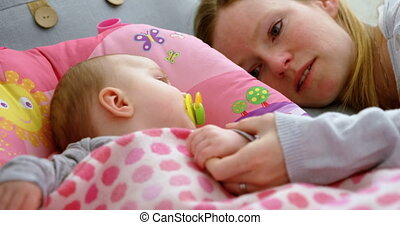 Mother putting his baby to sleep on baby bed 4k