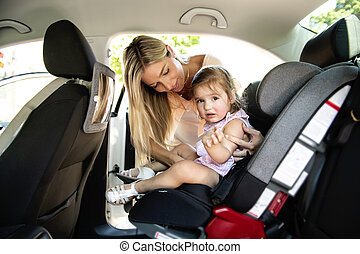 Mother putting his child daughter into her car seat in the car