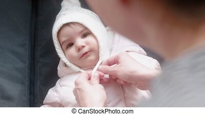 Mother putting tuque on her baby girl.