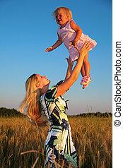 Mother raises child on hands in wheaten field