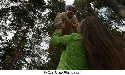 Mother raises the baby above him in the woods.