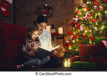 mother reading a book - Merry Christmas! Pretty young mother...