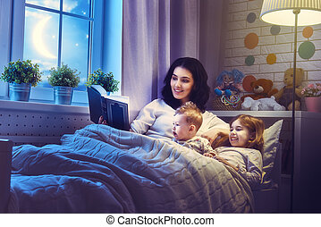 mother reading a book - Family reading bedtime. Pretty young...