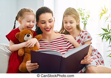mother reading a book to daughters