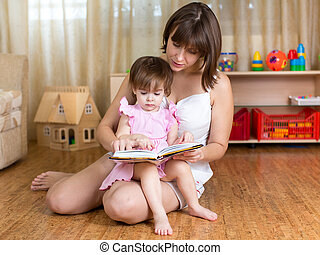 mother reading a book to kid at home