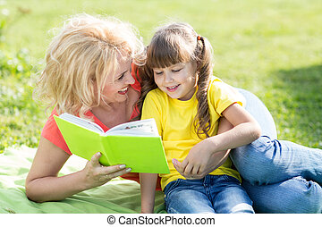 mother reading a book to kid outdoors in summertime