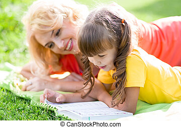 mother reading a book to kid outdoors in summer